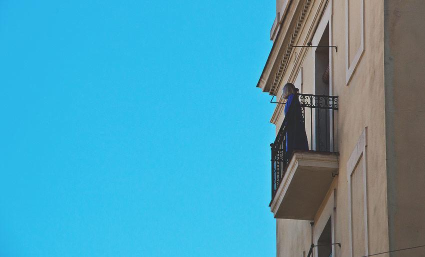 Ein Frau auf ihrem Balkon im Stadtteil Barceloneta